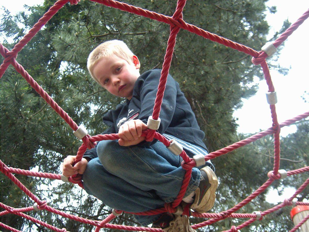 zu sehen ist ein von unten fotografierter kleiner Junge, der knieend von einem Spinnennetz eines Kinderspielplatzes gehalten wird, und in die Kamera schaut