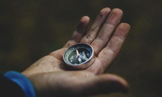 zu sehen ist die Aufnahme einer offenen ein wenig schmutzigen Kinderhand, in der ein Kompass liegt